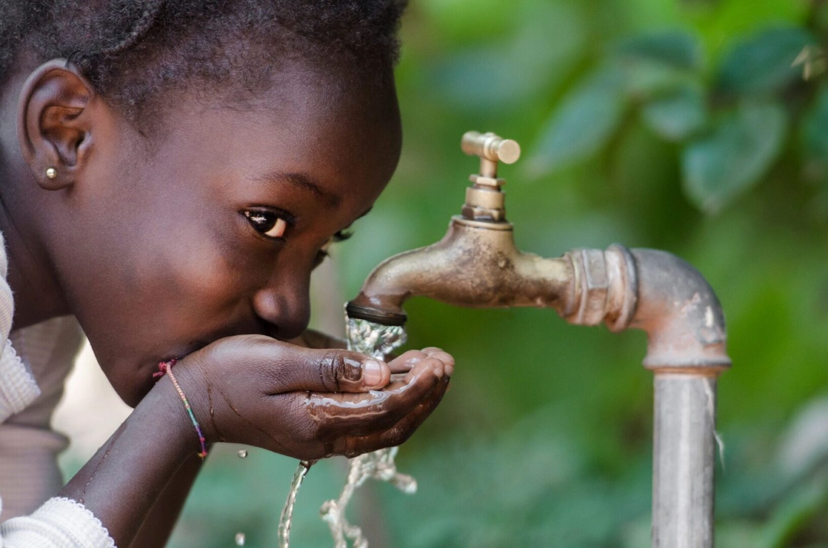 Girl Drinking Water in the Faucet